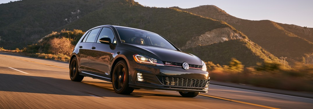 2019 Volkswagen Golf GTI driving down a highway at sunset