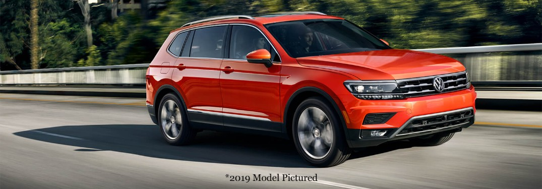 Front passenger angle of an orange 2019 Volkswagen Tiguan driving down a road with the disclaimer *2019 Model Pictured