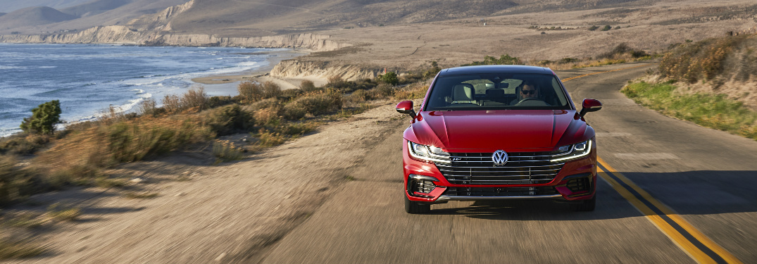 Red 2019 Volkswagen Arteon driving on a coastal road