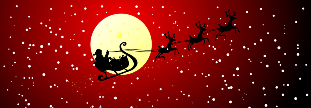 Silhouette of Santa with his reindeer flying in front of the moon