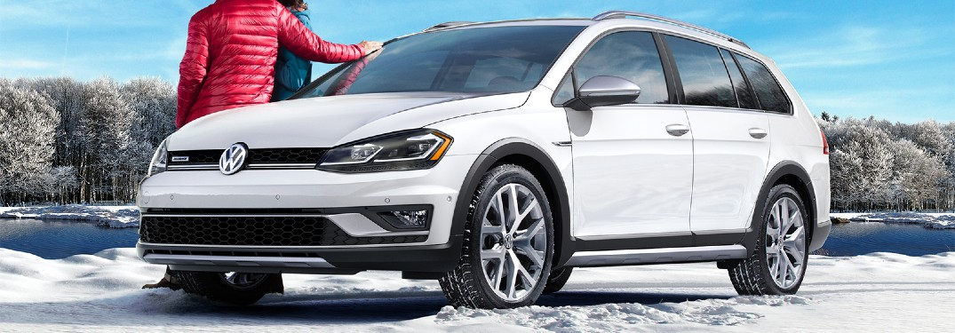 2019 Volkswagen Golf Alltrack white parked on snow by lake couple in coats