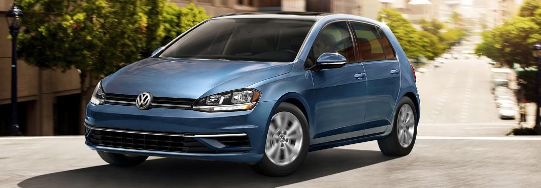 2020 Volkswagen Golf TSI blue driving toward shot on uneven city road