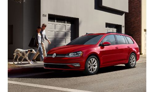 2019 Volkswagen Golf Sportwagen red parked by house woman and dog walking toward