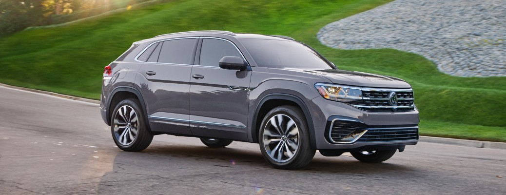 2020 Volkswagen Atlas Cross Sport dark grey driving around curve with green grass background