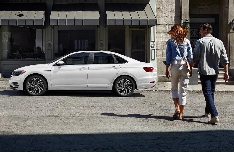 Two people walking towards the 2020 Volkswagen Jetta