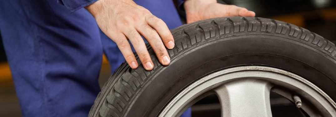 stock photo of person rolling tire by hand close up