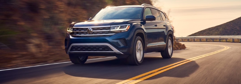 2021 Volkswagen Atlas blue driving around a corner in sunset light