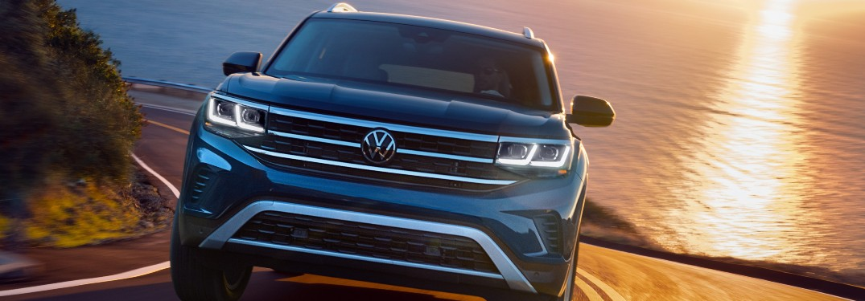 2021 Volkswagen Atlas blue driving toward shot with sunset water behind