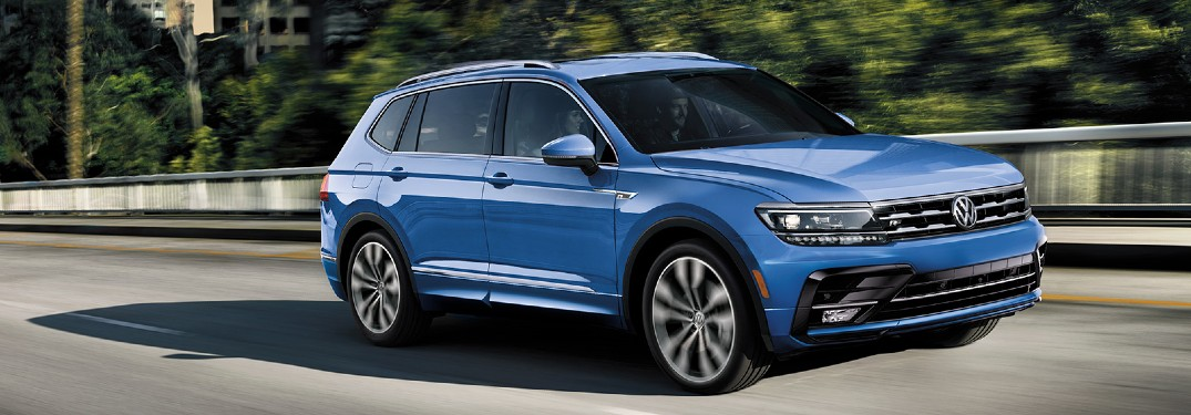 2020 Volkswagen Tiguan blue driving on bridge past trees