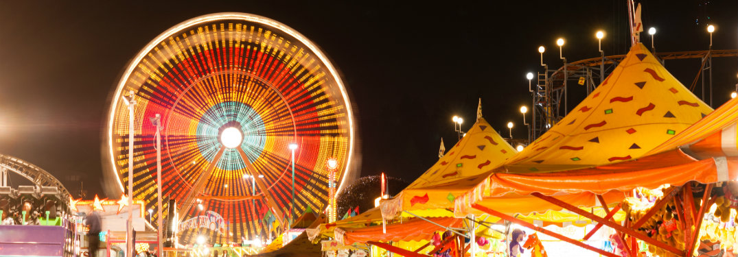 Ferris wheel and carnival tents at night