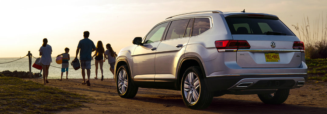 Rear of 2019 VW Atlas facing sunset as family walks toward beach