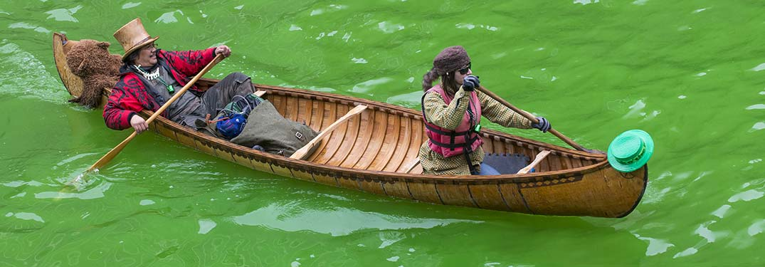 two people in a boat on a green river