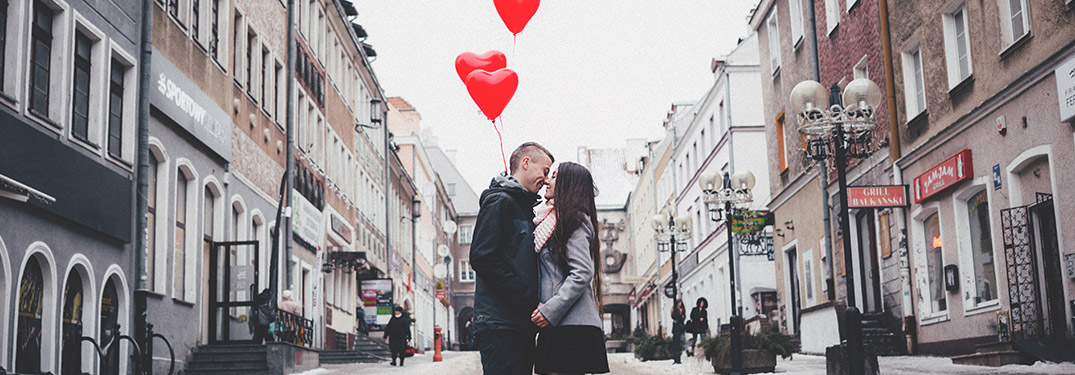 couple in a city with heart balloons