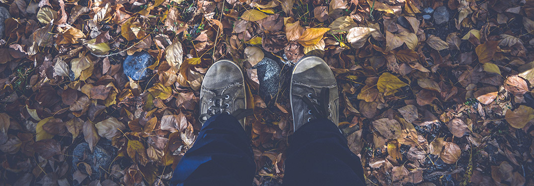 feet standing on fallen fall leaves