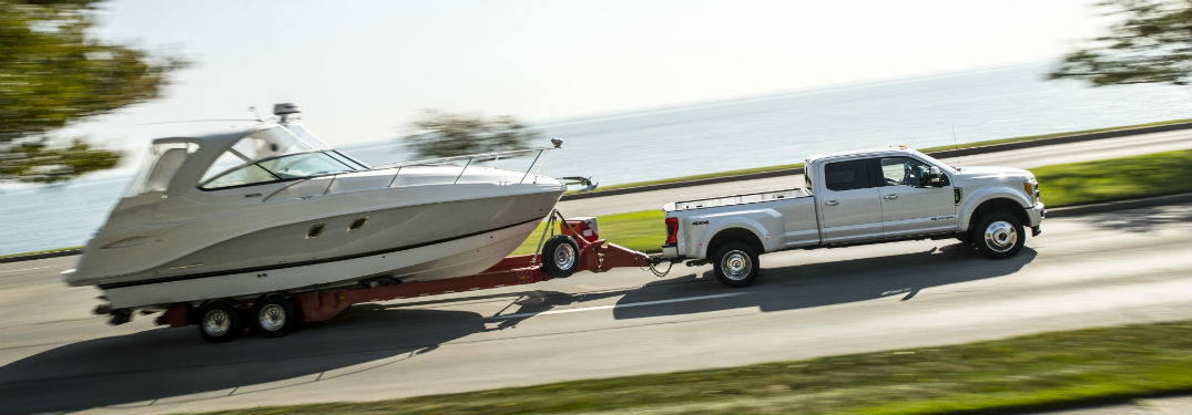White 2018 Ford F-250 Super Duty Limited 4x4 towing a boat on the road