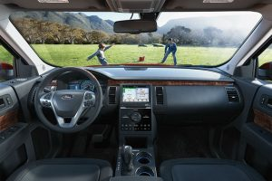 2018 Ford Flex driver dash and infotainment system with father and son seen playing through windshield