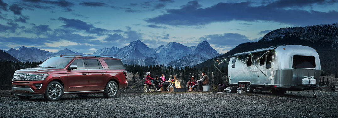 red 2018 Ford Expedition parked at a camp site with a family around a fire and a camper off to the side