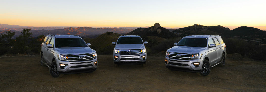 three silver 2018 Ford Expeditions parked on a mountain top with a sunset in the background