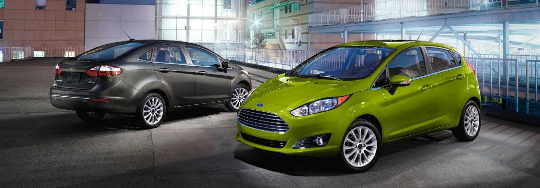 green 2018 Ford Fiesta Hatchback and black 2018 Ford Fiesta Sedan parked in the city surrounded by tall buildings