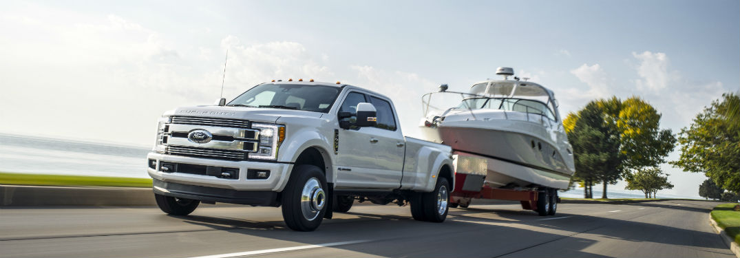 white 2018 Ford Super Duty towing a boat near a body of water