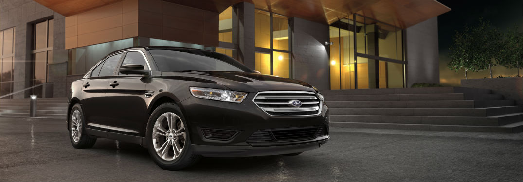 black 2018 Ford Taurus parked outside a modern looking building