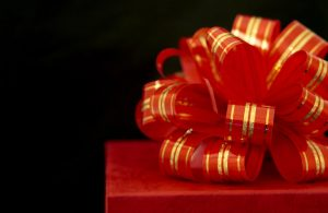 Christmas present with a red and gold bow on top
