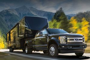 black 2018 Ford Super Duty towing a large RV