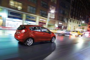 red 2018 Ford Fiesta Hatchback driving down a city street