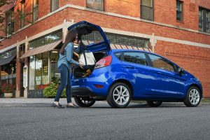 woman loading up the rear cargo area of her blue 2018 Ford Fiesta Hatchback