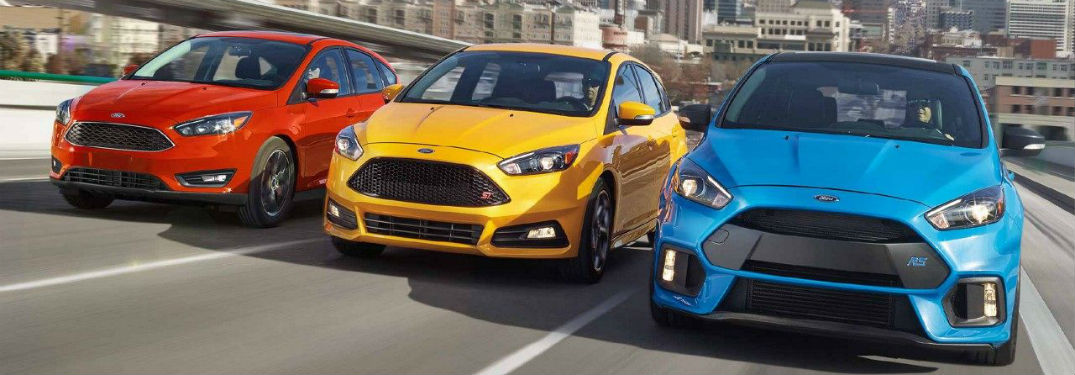 red, yellow and blue 2018 Ford Focus models driving side by side down the highway