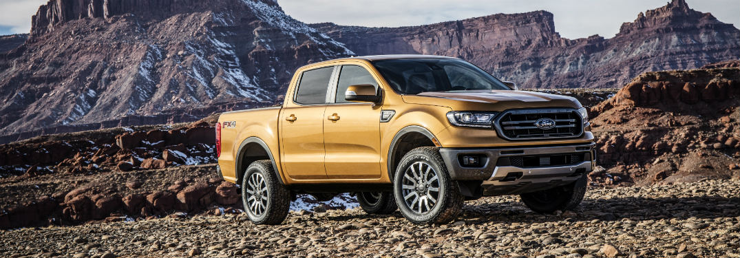 side view of a gold 2019 Ford Ranger parked on a rocky cliff with plateaus in the background