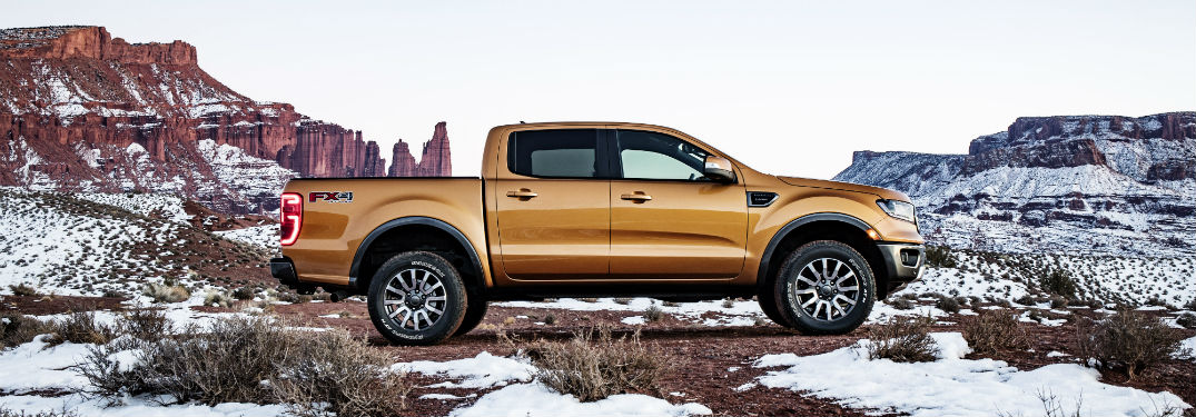 side view of a gold 2019 Ford Ranger parked on a snowy cliff
