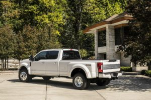 side view of a white 2018 Ford F-Series Super Duty Limited parked outside a house