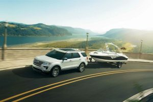 white 2018 Ford Explorer towing a boat along a coastal highway