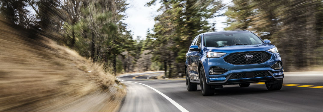 front view of a blue 2019 Ford Edge ST cruising along a wooded road