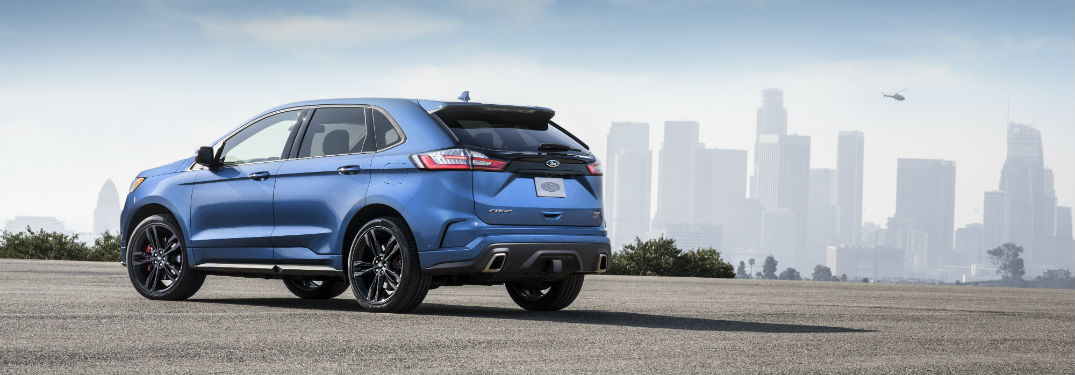 rear view of a blue 2019 Ford Edge ST with a city skyline in the background