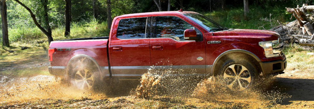 side view of a red 2018 Ford F-150 driving through a muddy puddle