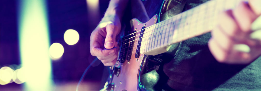 close up of hands playing a guitar