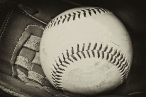 black and white photo of a baseball in a glove