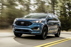 blue 2019 Ford Edge ST driving along a tree-lined road