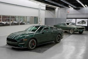 green 2019 Ford Mustang Bullitt parked with a green 1968 Ford Mustang GT Fastback parked in the background