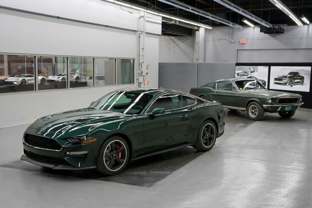 Green 2019 ford mustang bullitt parked with a green 1968 ford mustang gt fastback parked in