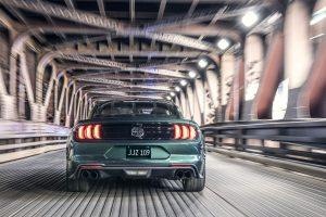 rear view of a green 2019 Ford Mustang Bullitt speeding through a tunnel