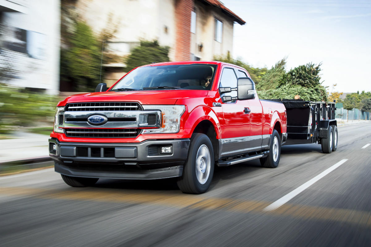 Red 2018 ford f 150 diesel towing a trailer down the road