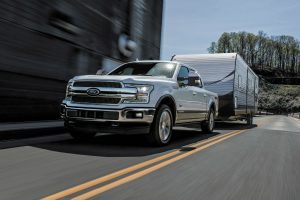 white 2018 Ford F-150 Diesel towing an RV