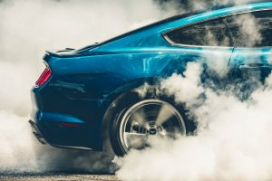 close up of the rear of a blue 2018 Ford Mustang GT in the middle of a burnout