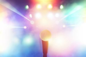 first person view of a microphone with bright colorful lights in the background