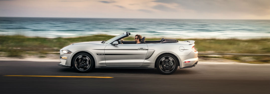 side view of a silver 2019 Ford Mustang GT driving along a coastal highway
