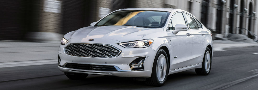 front view of a white 2019 Ford Fusion driving along a city street
