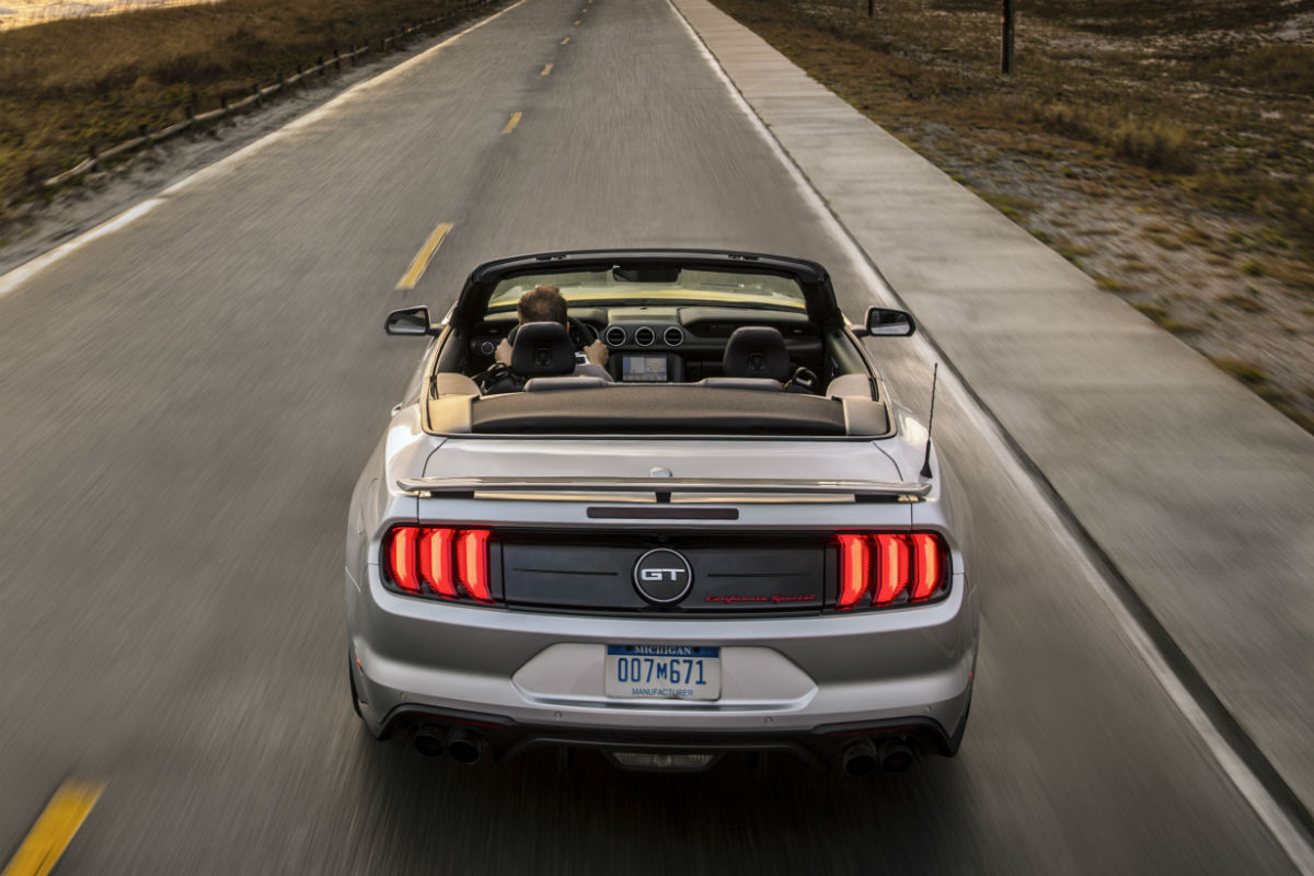 rear view of a silver 2019 Ford Mustang driving along a coastal highway